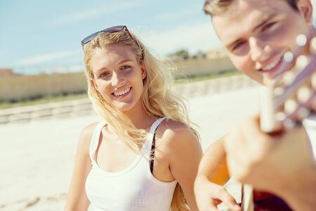 serenading: Happy romantic young couple playing guitar on beach in love Stock Photo