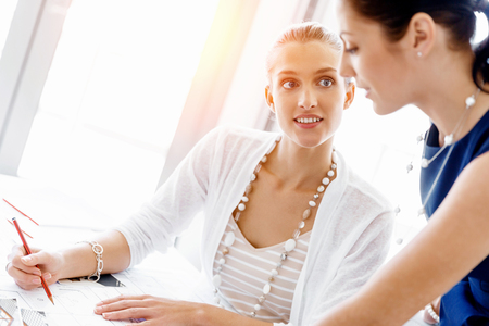 business woman: Two female colleagues working together in office