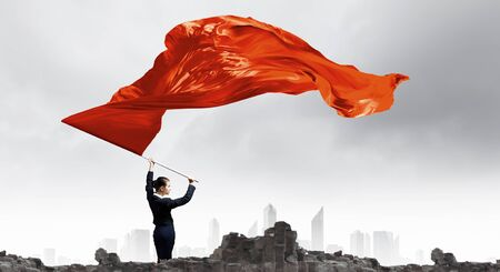 Young determined businesswoman with red flag in hands Stock Photo