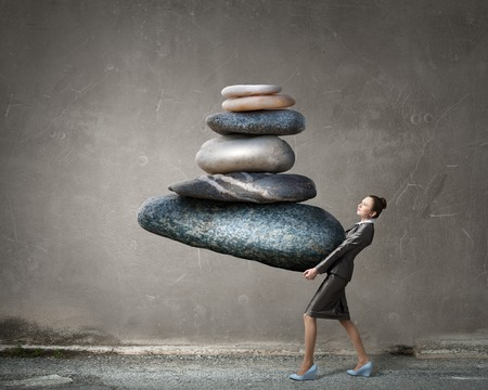Attractive businesswoman carrying stack of stones in hands