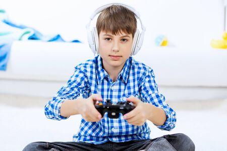 Emotional kid boy sitting on floor playing games on joystick