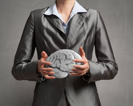 holding close: Close up of businesswoman holding brain concept in palms