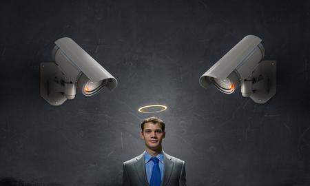 under control: Young businessman in room under CCTV camera control