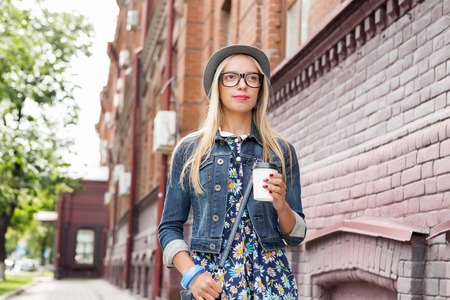 youthfulness: Happy tourist girl with coffee cup walking on city street