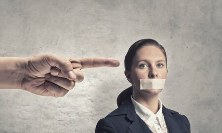 finger in mouth: Young speechless businesswoman with adhesive tape on mouth Stock Photo