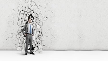 breaking through: Young powerful businessman breaking through cement wall