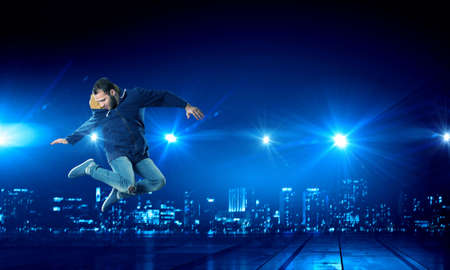 cool guy: Young dancer man in jump over dark background