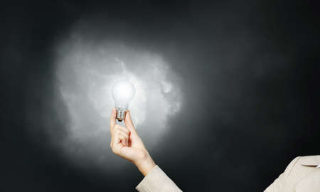 wattage: Glowing light bulb in person hand throwing light on darkness Stock Photo