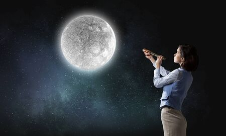 Young businesswoman looking in spyglass on full moon in sky