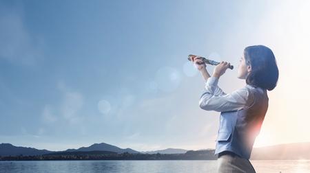 Empresaria joven que mira en catalejo en la salida del sol en el horizonte