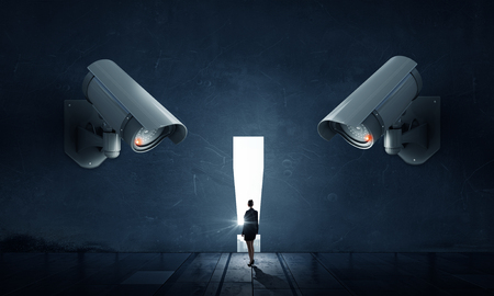 under control: Young businesswoman in room under CCTV camera control Stock Photo