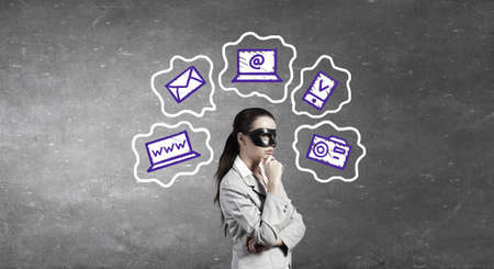 incognito: Young thoughtful businesswoman with black mask on face Stock Photo