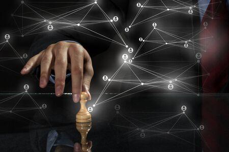 チェス盤の図を移動するビジネスマンの手に戦略コンセプト