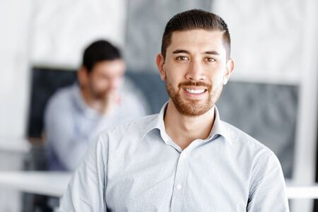attractive office: Young businessman sitting at desk in office