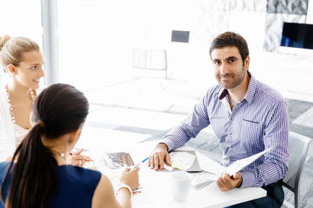 co operation: Business people working and discussing in modern office