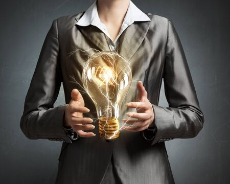 holding close: Close up of businesswoman holding glass glowing light bulb in hands