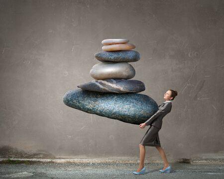 inner strength: Attractive businesswoman carrying stack of stones in hands