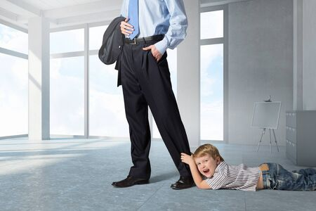 stay home work: Close up of legs of busy father going to job and his son praying him to stay Stock Photo