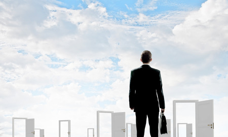 new entry: Businessman standing in front of opened doors and making decision Stock Photo