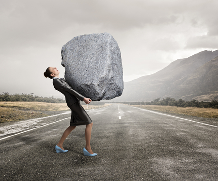 Attractive businesswoman carrying big heavy stone