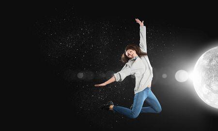 Tänzer der jungen Frau im Sprung über dunklem Hintergrund