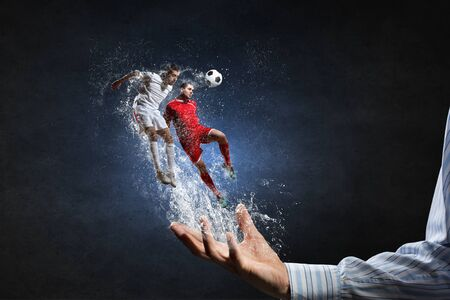 male palm: Two soccer players with ball in action in male palm Stock Photo