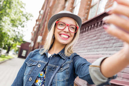 atraction: Woman taking selfie with smart phone in street of city