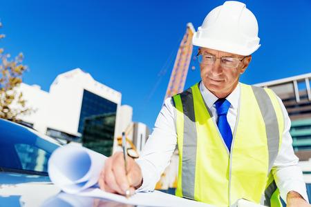 ingeniero civil: Ingeniero constructor con chaleco de seguridad con el modelo en el emplazamiento de la construcci�n