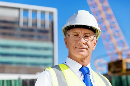 Ingenieursbouwer die veiligheidsvest met blocnote dragen bij bouwwerf Stockfoto
