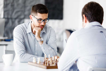 pawn adult: Portrait of two young man playing chess in office
