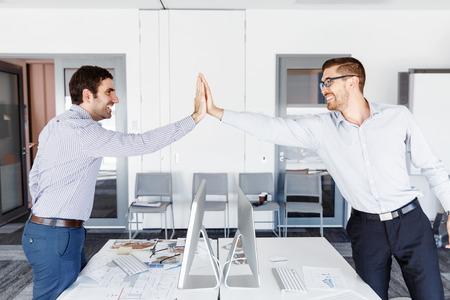 Twee knappe zakenman in bureau het vieren van de overwinning Stockfoto
