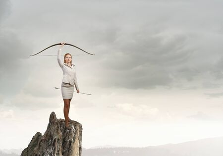 crossbow: Young woman archer in suit rising crossbow in hand Stock Photo