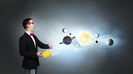 Young man splashing from bucket planets of space spinning around