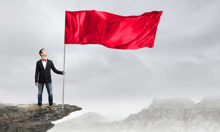 windy energy: Young man in bowtie with red waving flag on stick