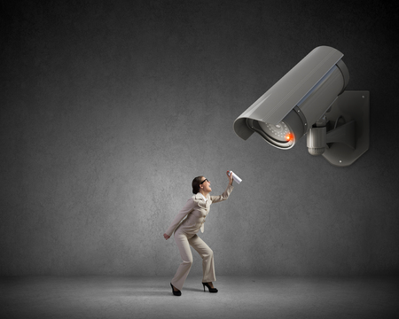 aerosol: Young woman spraying aerosol on CCTV camera control Stock Photo