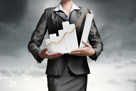 holding close: Close up of businesswoman holding increasing graph in hands Stock Photo