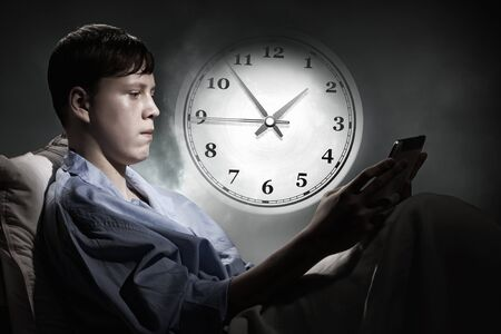 sleeping tablets: Teenager boy in bed using his tablet pc for entertainment