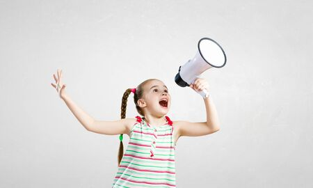 emotionally: Attractive kid girl screaming emotionally in megaphone Stock Photo