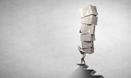 Businesswoman carrying with effort big stack of carton boxes