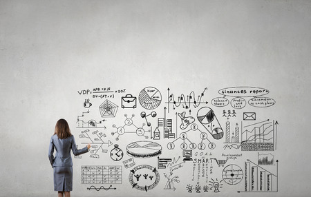 achieving: Businesswoman standing with back and drawing business development sketches for success achieving on screen Stock Photo