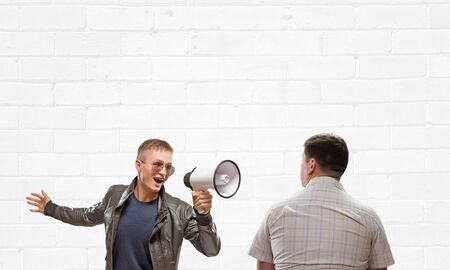 emotionally: Young man in casual screaming emotionally in megaphone Stock Photo