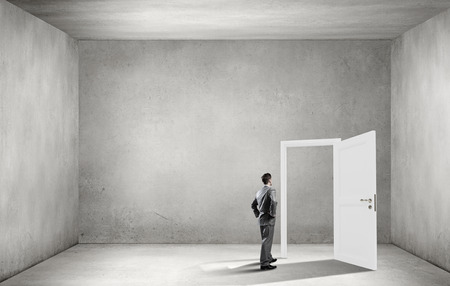 way out: Young businessman in concrete room and opened door with no way out Stock Photo