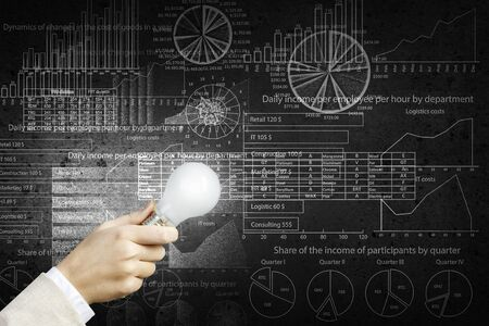 wattage: Glowing light bulb in person hand throwing light on business sketches Stock Photo