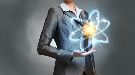 Close up of businesswoman holding glowing atom in hands