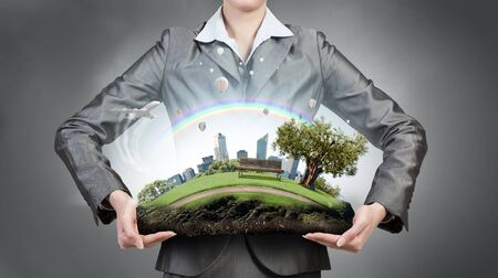 oxigen: Green eco life of modern city presented in hands of businesswoman