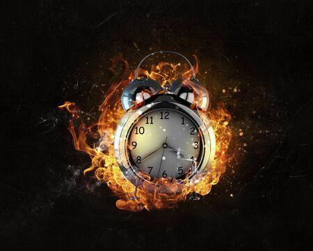oversleep: Alarm clock in fire flames on black background