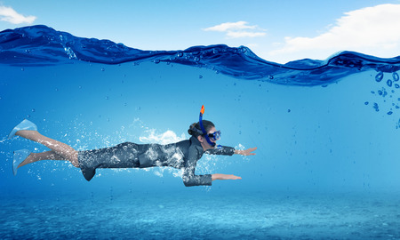 business challenge: Young businesswoman in suit and diving mask swimming under water