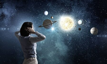 Young woman covering her ears with hands and looking at space planets Stock Photo