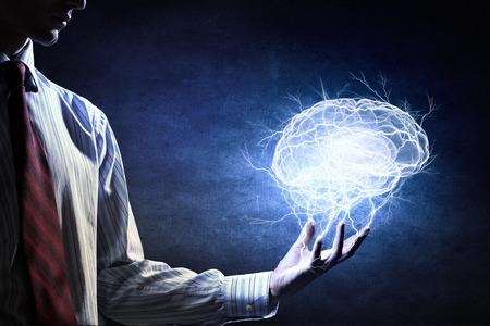 Dłoń na ciemnym tle gospodarstwa z ostrożnością mózgu świecące symbolu