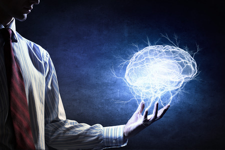 Hand op donkere achtergrond houden met zorg het gloeiende symbool van de hersenen